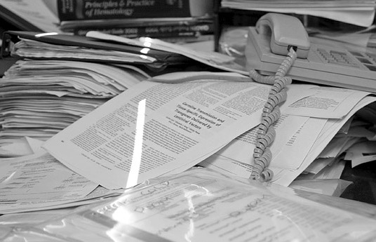 A pile of paperwork on a desk, with an old style phone and a stream of light artistically highlighting the paper.
