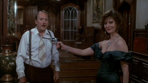 A shot from the film Clue, where Mrs. White holds a gun in front of Col. Mustard